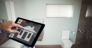 Hand using smart home app on tablet PC in washroom Royalty Free Stock Images