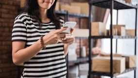 Free Hand Using Smart Phone And Packages Shelf In Background Stock Image - 129834111