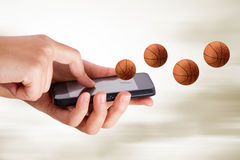 Hand Using Smart Phone with Basketball Subject Stock Photos