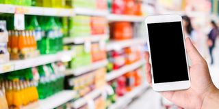 Hand using smart phone with blank screen over blur supermarket, Royalty Free Stock Photos