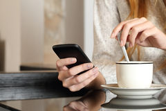 Hand using a smart phone during breakfast at home Royalty Free Stock Photo