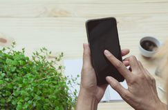 Hand using smart phone on wooden table background. Technology an Royalty Free Stock Image