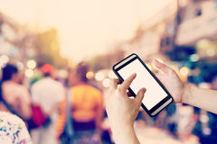 Hand using smartphone and Blurred crowd of people walking throug Royalty Free Stock Photo
