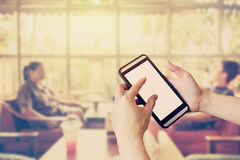 Hand using smartphone and Blurred people in coffee shop with vin Royalty Free Stock Photo