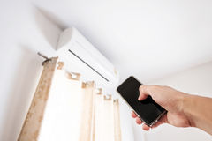Hand using smartphone controlling air conditioning Stock Photo