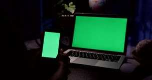 Hand using smartphone and a laptop computer with green screen . Dolly in. Hand is using smartphone and a laptop computer with green screen . Dolly in stock video footage