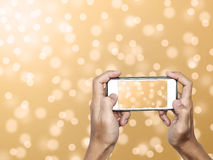 Hand using Smartphone taking a Photo of Defocus Gold Bokeh Lights Background Stock Photography