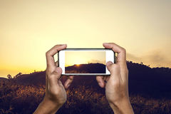 Hand using smartphone taking photo of tropical mountain landscape in sunset royalty free stock image