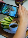 Hand using a smartphone to photograph fried Vietnamese pancakes - nem stock photography