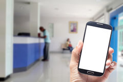 Hand using smartphone with white screen on blurred bank counter. Background Stock Image