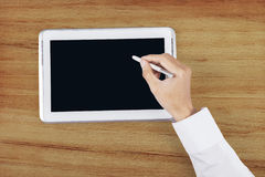 Hand using stylus pen on digital tablet. Close up of businessman hand using stylus pen for touching the digital tablet screen Stock Photos