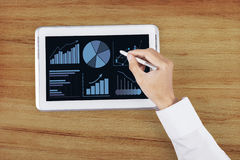 Hand using stylus pen on digital tablet 2. Man hand using stylus pen for touching the digital tablet with business chart on a screen Stock Photos