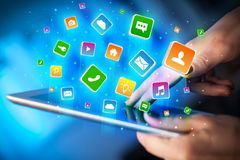 Hand using tablet with application icons flying around Royalty Free Stock Photo
