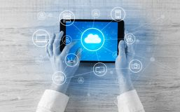 Hand using tablet with centralized cloud computing system concept. Hand touching tablet with cloud computing and online storage conceptn stock photography