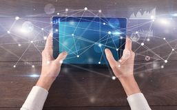 Hand holding tablet with linked graphs and charts concept. Hand using tablet with linking graphs charts  report and informational flow concept royalty free stock photography