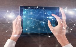 Hand holding tablet with linked graphs and charts concept. Hand using tablet with linking graphs charts report and informational flow conceptn royalty free stock photo