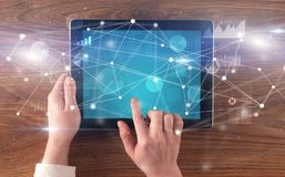 Hand holding tablet with linked graphs and charts concept. Hand using tablet with linking graphs charts  report and informational flow conceptn royalty free stock images