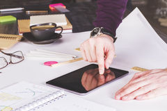 Hand using tablet. Male hand using tablet placed on large whatman with office tools Stock Image