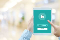 Hand using tablet with password login on screen, cyber security Stock Image