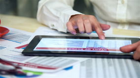 Hand Using Touch Pad With Financial Report stock footage