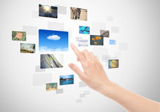Hand Using Touch Screen Interface With Pictures. Woman hand using touch screen interface with pictures in frames Royalty Free Stock Photography