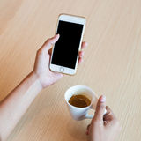 Hand using a touch screen of white smartphone on the wooden table and hand holding aromatic cappuccino Royalty Free Stock Photo