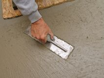 Hand using trowel to finish concrete slab Stock Photo