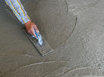 Hand using trowel to finish wet concrete floor Royalty Free Stock Photos