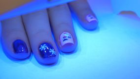 UV lamp gel polish manicure process in home conditions. New Year`s manicure. Hand in UV Lamp Nail Dryer. Woman Drying Nails. A manicure in the salon. Manicure in stock footage