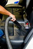 Hand vacuum cleaning dirt on a back car seats Stock Images