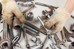 Hand van arbeider in handschoenen met hulpmiddelen om machines in workshop te herstellen royalty-vrije stock foto's