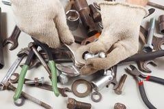 Hand van arbeider met in handschoenen die delen van het mechanisme in workshop herstellen stock afbeeldingen