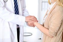 Hand van arts die haar vrouwelijke patiënt geruststellen Medisch ethiek en vertrouwensconcept stock afbeelding