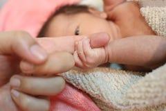 Hand van Aziatische baby die bij vingers van moeder wordt gearresteerd royalty-vrije stock foto