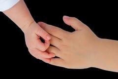 Hand van baby wat betreft hand van kind op zwarte Royalty-vrije Stock Foto