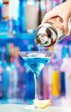 Hand van barman gietende likeur aan cocktailglas stock fotografie