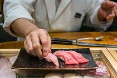 Hand van Chef-kok die zeevruchten en ruwe gesneden vissenopslag bij het overzeese voedselmarkt van Tsukiji, Japan voorbereiden stock fotografie