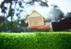 Hand van de bedrijfsmens en houten huismodel op mooie groene gra stock afbeelding