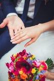Hand van de bruidegom en de bruid met trouwringen Stock Afbeeldingen