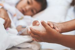 Hand van de de holdings de zieke jonge zuster van het kindmeisje die IV die oplossing hebben met liefde en zorg wordt verbonden royalty-vrije stock foto's