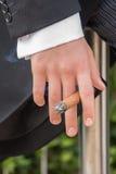Hand van de mens in staarten die sigaar houden Stock Fotografie