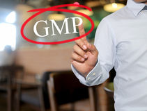 Hand van de mens wat betreft tekst GMP met witte kleur op onduidelijk beeldbinnenland Stock Afbeeldingen