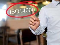 Hand van de mens wat betreft tekst ISO14000 met witte kleur bij het onduidelijke beeld inte Stock Afbeelding