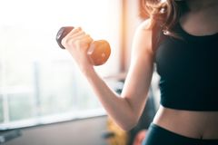 Hand van de opheffende domoor van de sportenvrouw voor gewichtheffen dichtbij w Royalty-vrije Stock Afbeelding