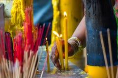 Hand van de Oude kaarsen van de vrouwen brandende verlichting voor gebeden buiten de Tempel Royalty-vrije Stock Afbeelding
