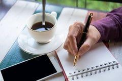 Hand van de pen die van de bedrijfsmensenholding op notitieboekjedocument schrijven Fron Stock Fotografie
