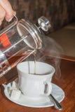 Hand van de persoon die wat thee in een mok geven stock fotografie