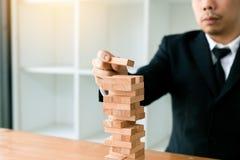 Hand van de stapelsspel van zakenman speelhoutsneden met de planning van strategie van projectleiding stock afbeelding
