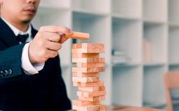 Hand van de stapelsspel van zakenman speelhoutsneden met de planning van strategie van projectleiding royalty-vrije stock afbeeldingen