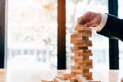 Hand van de stapelsspel van zakenman speelhoutsneden met de planning van strategie van projectleiding stock afbeeldingen